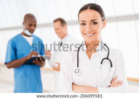 Confident female doctor. Beautiful female doctor keeping arms crossed and smiling while her colleagues talking in the background