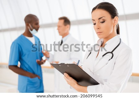 Confident female doctor. Beautiful female doctor writing something at her clipboard while her colleagues talking in the background - stock photo
