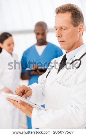 Confident female doctor. Confident medical doctor working on digital tablet while his colleagues talking in the background - stock photo