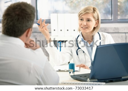 Confident female doctor discussing diagnosis with patient in office, smiling.? - stock photo