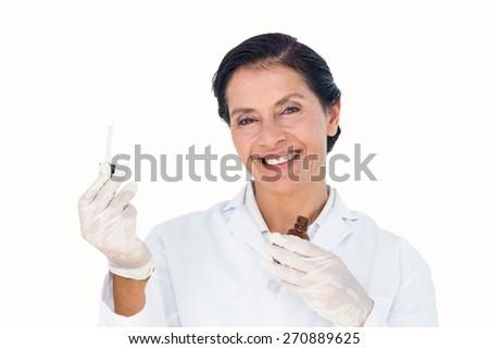 Confident female doctor holding medicine bottle on white background - stock photo