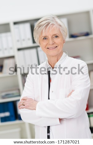 Confident female doctor or nurse in an office standing in a white lab coat smiling at the camera with folded arms - stock photo