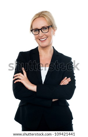 Confident female executive wearing eyeglasses, posing with arms crossed - stock photo