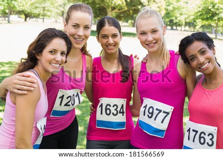Confident female participants of breast cancer marathon standing together in park - stock photo