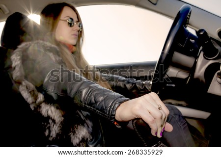 Confident female racer drives car. Young woman drives car, focus on her hand switching transmission grip. Vintage stylized - worm tones, sepia filter applied - stock photo