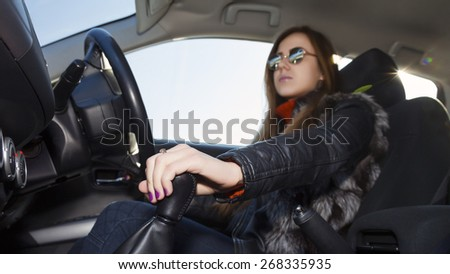 Confident female racer drives car. Young woman drives car, focus on her hand switching transmission grip Biker dress black leather jacket, sunglasses, bright sunbeams on right corner - stock photo
