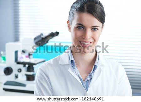 Confident female researcher in the chemistry lab with microscope and laboratory glassware on background. - stock photo