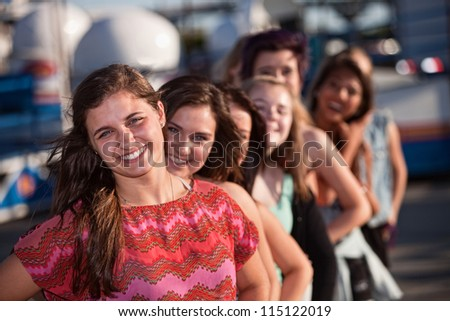 Confident female teenager with group of friends outdoors - stock photo