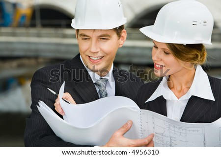 Confident female worker is showing a architectural plan to her chief - stock photo