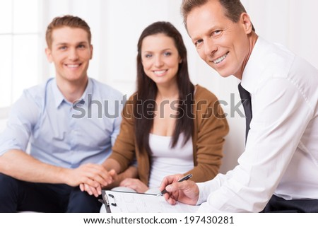 Confident financial expert. Confident mature man in shirt and tie looking at camera and smiling while couple sitting in the background and smiling  - stock photo