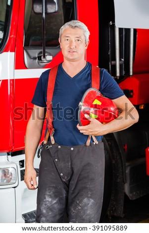 Confident Firefighter Holding Red Helmet - stock photo