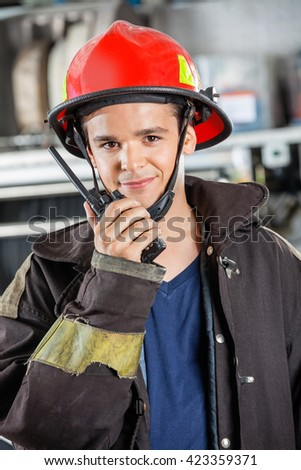 Confident Firefighter Using Walkie Talkie At Station - stock photo