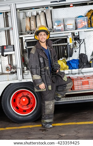 Confident Fireman Standing By Truck At Station - stock photo