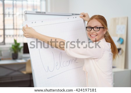 Confident friendly businesswoman preparing a presentation pinning a Welcome sheet of paper to a clipboard in the office - stock photo