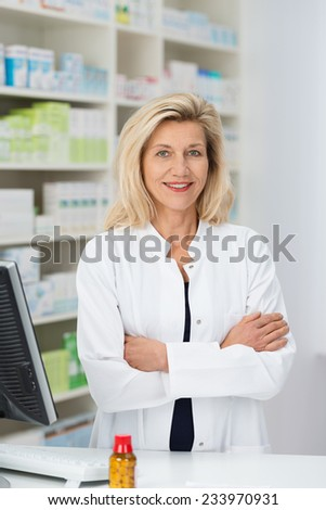 Confident friendly female pharmacist standing with folded arms smiling at the camera behind her desk in the pharmacy - stock photo