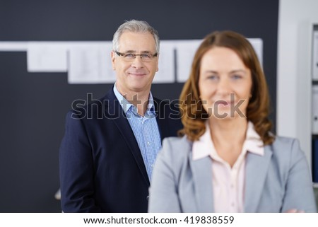 Confident friendly male business executive wearing glasses standing behind a female colleague smiling at the camera, focus to him - stock photo