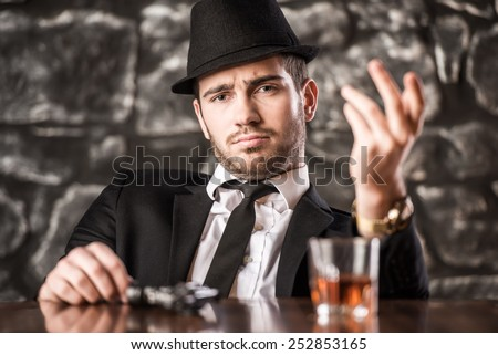 Confident, gangster man in suit and hat is sitting at the table with a glass of whisky and gun. - stock photo