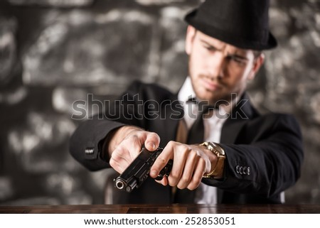 Confident, gangster man in suit and hat is sitting at the table with a gun. - stock photo