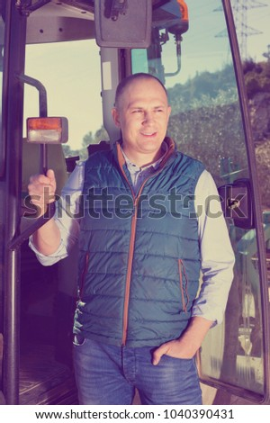Confident glad cheerful positive male owner of vineyard posing near tractor outdoors in sunny day
