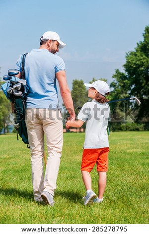 Confident golf players. Rear view of young man and his son holding hands and looking at each other while walking on the golf course - stock photo