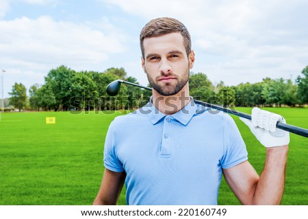 Confident golfer. Confident young male golfer holding driver and looking at camera while standing on green - stock photo