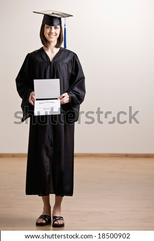 Confident graduating student wearing cap and gown holding diploma - stock photo