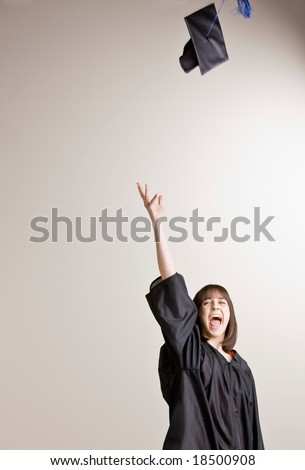Confident graduating student wearing cap and gown throwing cap in air - stock photo