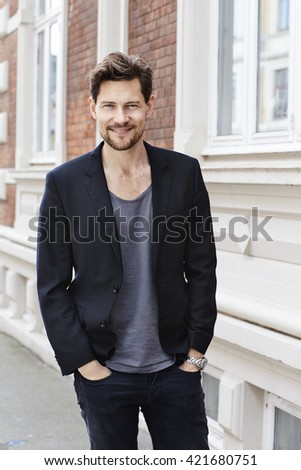Confident guy smiling at camera - stock photo