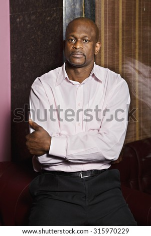 Confident guy wearing pink shirt at glass wall arms folded - stock photo