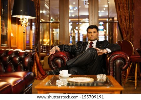 Confident handsome brunette sitting in luxury interior  - stock photo