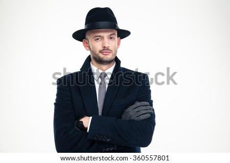 Confident handsome business man in coat, hat and gloves standing over white background - stock photo