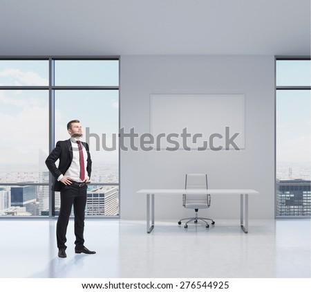 Confident handsome businessman is standing in the modern office in New York. Workplace with a table and a chair. - stock photo