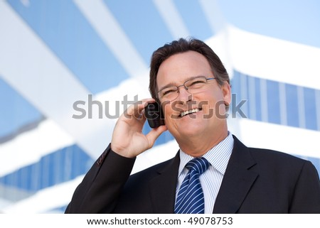 Confident, Handsome Businessman Smiles as He Talks on His Cell Phone. - stock photo