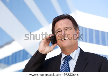 Confident, Handsome Businessman Smiles as He Talks on His Cell Phone Outdoors. - stock photo