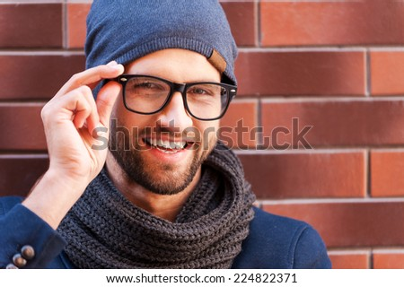 Confident handsome. Handsome young man in smart casual wear adjusting his eyeglasses and smiling while standing against the brick wall - stock photo