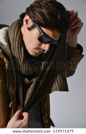 Confident handsome man in sunglasses and leather jacket-gray background