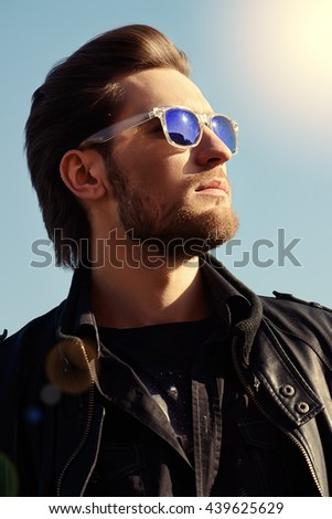 Confident handsome man in sunglasses and leather jacket over blue sky. Men's beauty, fashion. Outdoor portrait. - stock photo