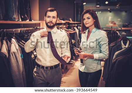 Confident handsome man with beard choosing a tie in a suit shop. - stock photo