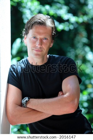 Confident, handsome middle aged man leaning against wall in the sun and smiling at camera - stock photo