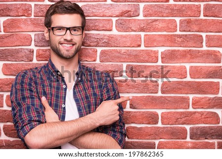 Confident handsome pointing your advertising. Handsome young man keeping arms crossed and pointing at copy space while standing against brick wall