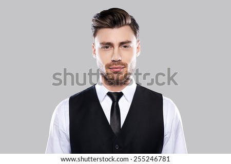 Confident handsome. Portrait of handsome young man in formalwear looking at camera while standing against grey background - stock photo