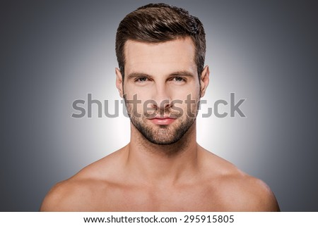 Confident handsome. Portrait of handsome young shirtless man looking at camera while standing against grey background