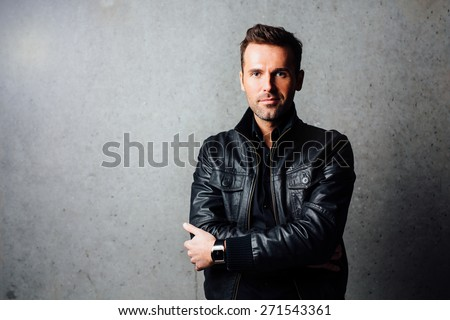 Confident handsome young man in leather jacket standing against concrete wall - stock photo