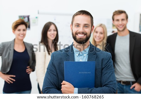 Confident happy businessman clutching a file containing his curriculum vitae to his chest beaming broadly with excitement as he stands in front of his colleagues or business team - stock photo