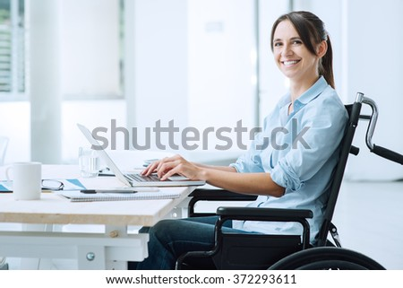 Confident happy businesswoman in wheelchair working at office desk and using a laptop, she is smiling at camera, disability overcoming concept - stock photo