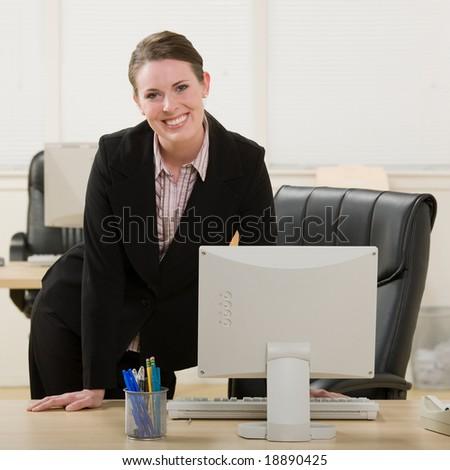 Confident, happy businesswoman leaning on desk - stock photo