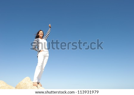Confident, happy, successful and attractive mature, senior woman on top of rock, mountain, isolated with blue sky as background and copy space.