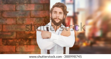 Confident hipster pointing sideways with arms crossed against wall of a house - stock photo