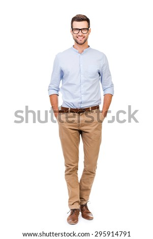 Confident in any situation. Happy young man holding hands in pockets and looking at camera while standing against white background - stock photo