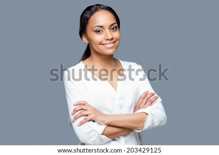 Confident in her beauty. Portrait of attractive young African woman keeping arms crossed and smiling while standing against grey background - stock photo